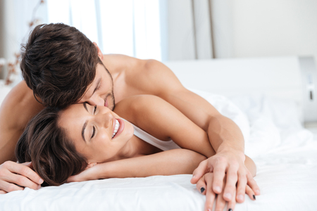 Young lovely couple in love on the bed in bedroom Stock Photo
