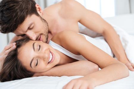 Primer plano retrato de una hermosa pareja sexy besar en la cama