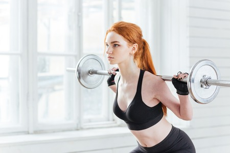 squats: Close-up portrait of a fitness young woman doing squats with barbell at the gym