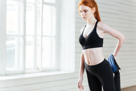 exercices: Young beautiful fitness woman doing stretching exercices at the gym