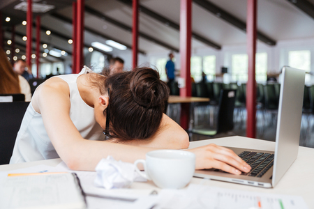 sad eyes: Exhausted fatigued young business woman sleeping on table with laptop at workplace Stock Photo