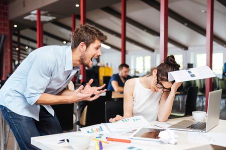 Mad gekke jonge zakenman ruzie met droevige gewezen zakenvrouw aan het werk in het kantoor