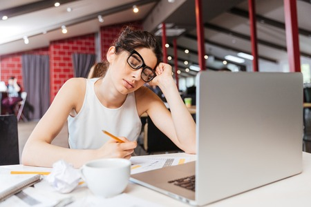 abatis: Tired sleepy young business woman in glasses sitting and working with laptop in office Stock Photo