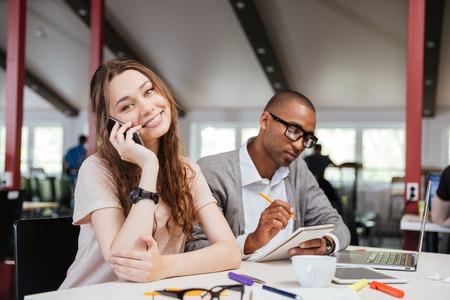 hablando por celular: Alegre hermosa joven mujer de negocios hablando por teléfono celular y de trabajo con el hombre africano seus en la oficina