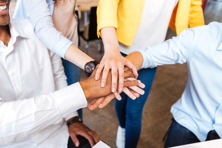 join the team: Closeup of multiethnic group of young people standing and joining hands Stock Photo