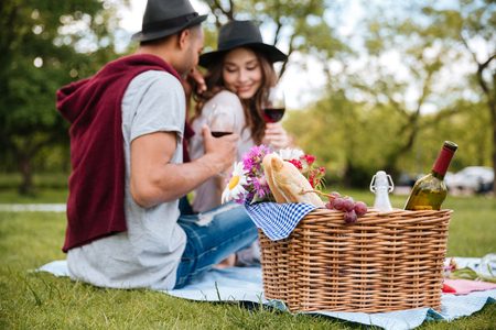 adult's: Basket with food and drinks standing near tender young couple drinking wine in park