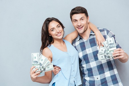 Happy young couple showing their money isolated on gray background