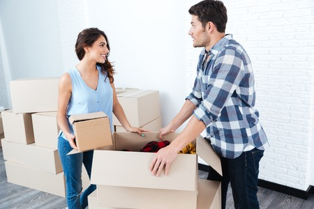 unpacking: Young pretty happy married couple unpacking in new flat Stock Photo