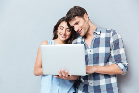 Portrait of happy young couple using laptop isolated on gray background Stock Photo