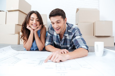 house blueprints: Happy couple looking at new house blueprints at home Stock Photo