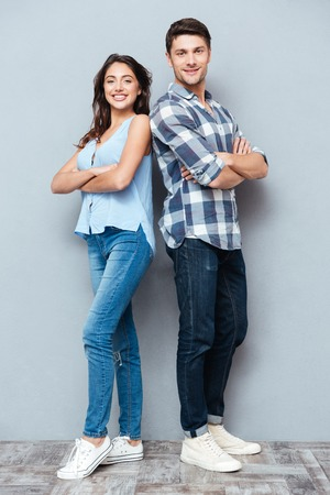 Attractive teenage couple standing back to back with arms crossed isolated on gray background Stock Photo