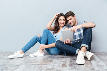 cute guy: Happy young couple using tablet sitting on the floor at home isolated on gray background