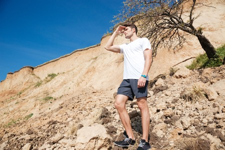 far away: Handsome young man standing outdoors and looking far away Stock Photo
