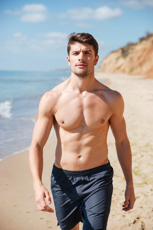 Closeup of confident shirtless young man walking along the beach
