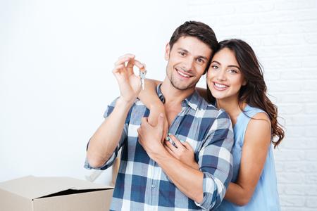 Jong lachend stel met sleutels voor nieuwe huis knuffelen kijken naar camera
