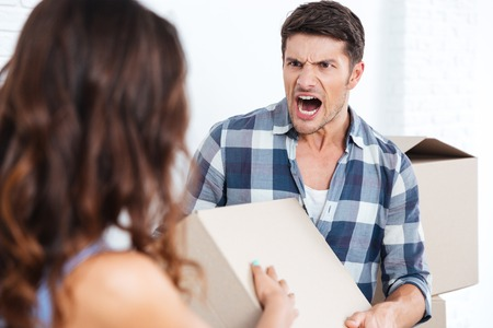 relocation: Young married couple arguing during relocation in new house