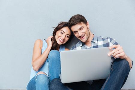 행복 한 젊은 부부 노트북의 초상화 회색 배경에 고립 스톡 콘텐츠