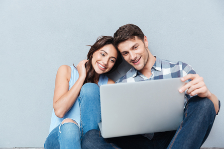 Portrait of happy young couple using laptop isolated on gray background 免版税图像