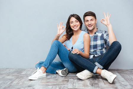 sittting: Close up of young happy couple giving thumbs up isolated on gray background Stock Photo
