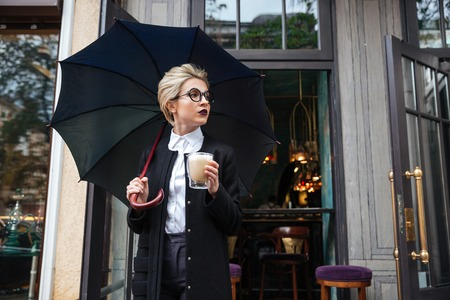 Mujer hermosa joven con el paraguas y taza de café al aire libre de pie en el café Foto de archivo