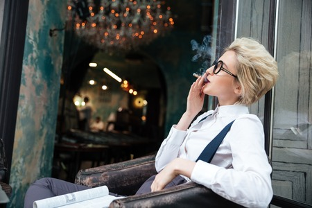 junky: Relaxed young woman sitting and smoking cigarette in cafe Stock Photo