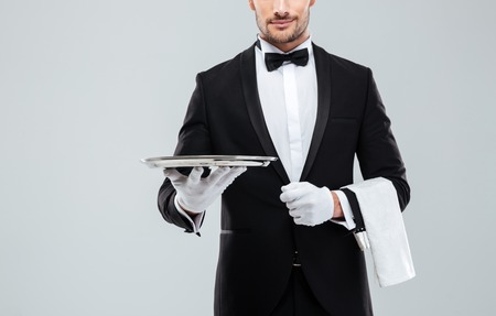 lapel: Closeup of young waiter in tuxedo holding metal empty tray and napkin Stock Photo