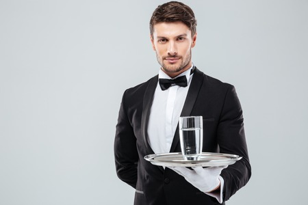 white suit: Portrait of waiter in tuxedo and gloves holding glass of water on metal tray Stock Photo