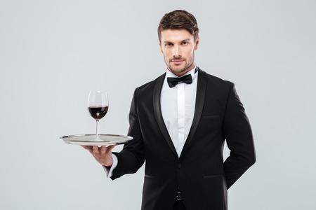 finesse: Portrait of young waiter in tuxedo holding glass of red wine on silver tray Stock Photo