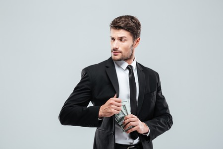 theif: Serious young businessman in suit and tie hiding money in pocket over white background