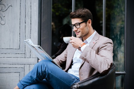 concetrated: Smiling young man in glasses drinking coffee and reading magazine in outdoor cafe