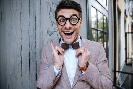 unfashionable: Portrait of cheerful funny young man in round glasses and wooden bowtie standing outdoors