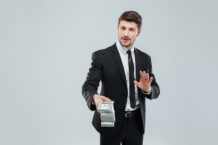 money exchange: Attractive young businessman in suit and tie giving you money back over white background Stock Photo