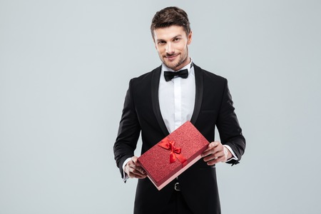 Confident attracive young man in tuxedo standing and holding gift box