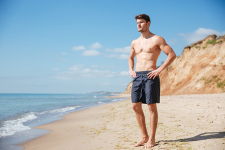 athletic body: Handsome relaxed young man in black shorts standing on the beach Stock Photo