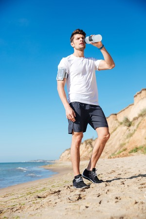 Handsome young sportsman standing and drinking water on the beach
