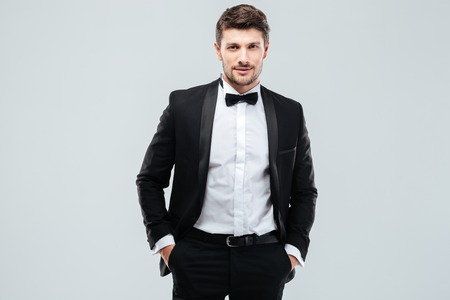Confident young man in tuxedo with bowtie standing with hands in pockets
