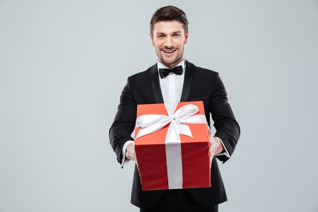 gigolo: Cheerful attractive young man in tuxedo giving you red gift box