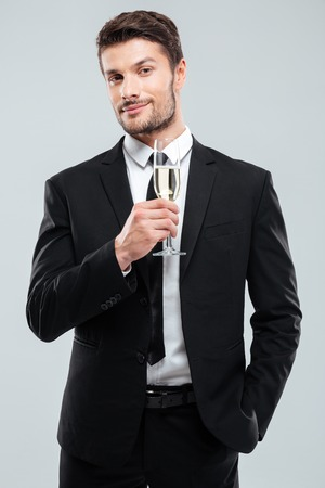 Portrait of attractive young businessman in suit and tie with glass of champagne over white background