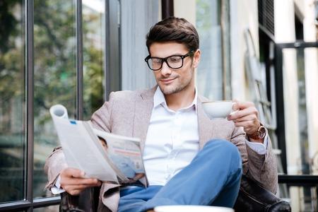 Knappe jonge man in glazen met het tijdschrift koffie drinken in de buitenlucht cafe
