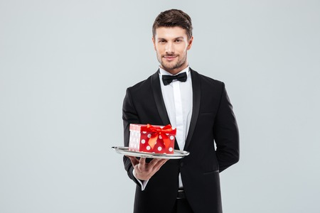 Handsome young butler in tuxedo with bowtie gift box on tray Stock Photo