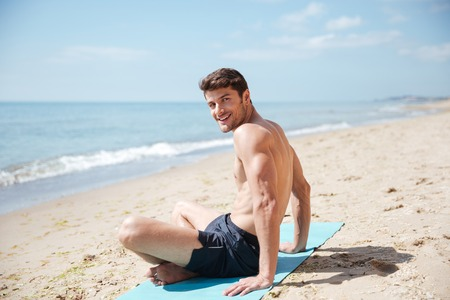 muscular body: Happy attractive young man sitting with legs crossed on the beach Stock Photo