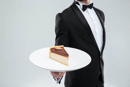 piece of cake: Waiter in tuxedo with bowtie holding plate with piece of cake