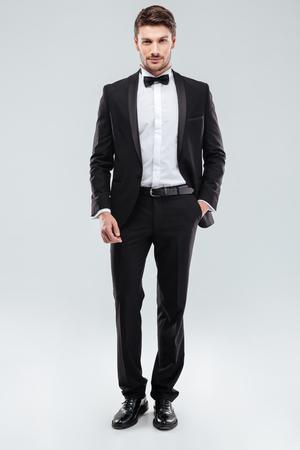 ポケットに手でタキシードな地位に自信を持って魅力的な若い男