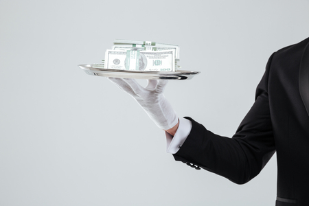 Closeup of tray with money holded by waiter hand in glove