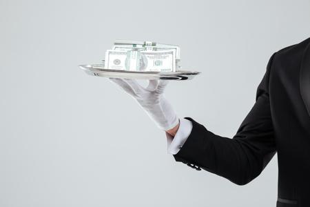 De close-up van dienblad met geld holded door kelner dient handschoen in