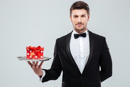 hand cuff: Attractive young waiter in tuxedo with bowtie holding present box on tray
