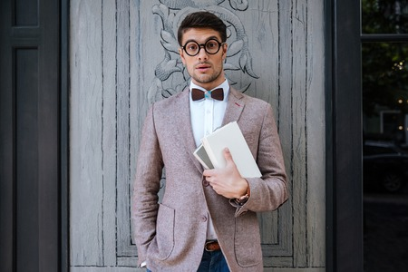 nerd glasses: Young fashion man with nerd glasses and stylish hairdo in jacket posing Stock Photo