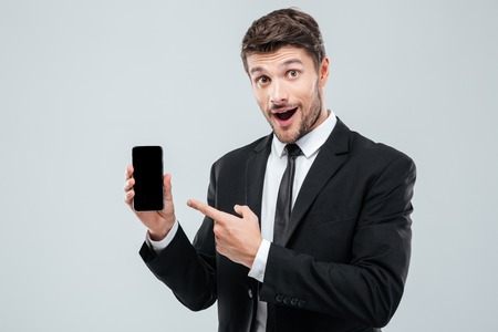 telephone salesman: Amazed young businessman holding and pointing on blank screen smartphone over white background Stock Photo