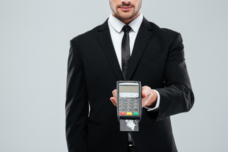 Businessman in black suit and tie holding bank terminal with credit card over white background