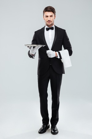 Full length of confident young waiter in tuxedo standing and holding tray